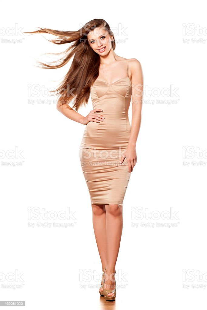 Long haired woman in nude midi dress on a white background stock photo