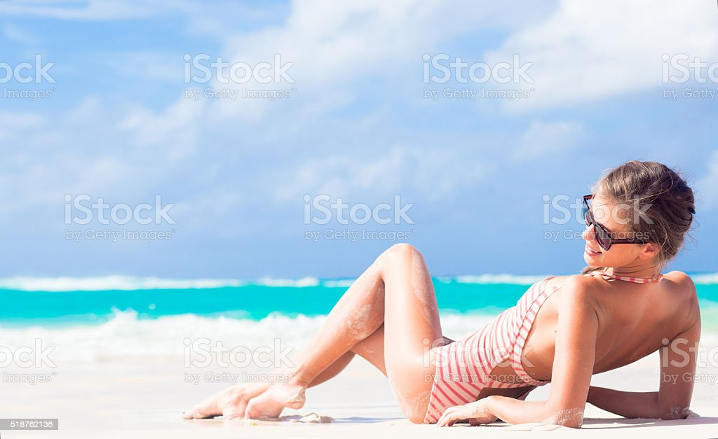 long haired woman in red swimsuit on tropical caribbean beach stock photo