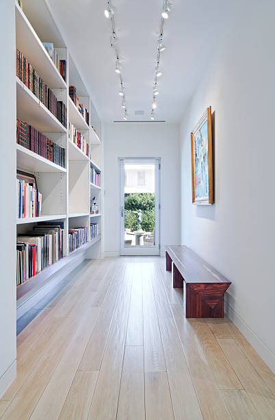 Long Hallway with Built-in Bookcase Leading to Outdoors stock photo