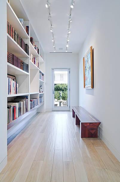 long hallway with built-in bookcase leading to outdoors - entré bildbanksfoton och bilder