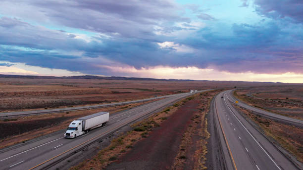 Long Haul Freight Hauler Semi-Truck and Trailer Traveling on a Four-Lane Highway in a desolate desert at dusk or dawn stock photo