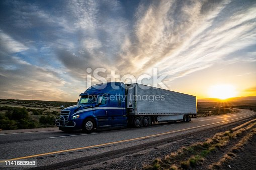 Lone truck with semi-trailer at sunset on a desert highway