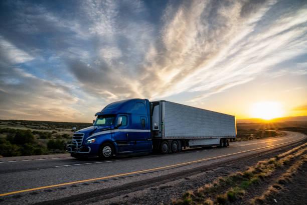 caminhão semi do curso longo em uma estrada no crepúsculo um céu dramático - meio de transporte - fotografias e filmes do acervo