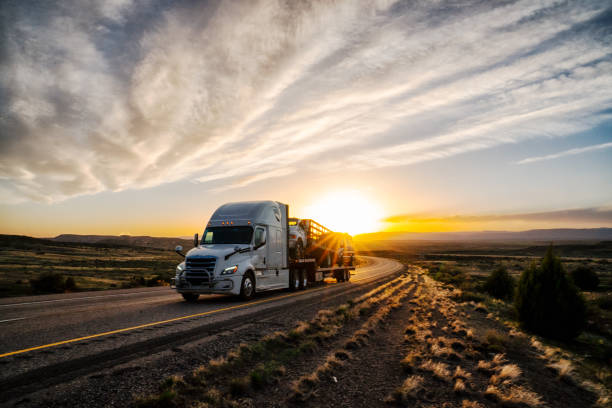Long Haul Semi Truck on a Highway at Dusk under a Dramatic Sky stock photo