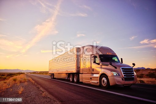 Large semi truck hauling freight on the open highway in the western USA under an evening sky.