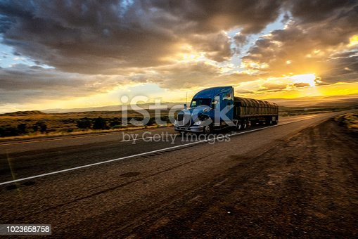 Big freight truck on the open highway in front of an amazing sunset
