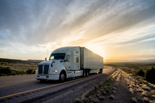 Long Haul Semi Truck Speeding Down a Four Lane Highway in a Beautiful Sunset stock photo
