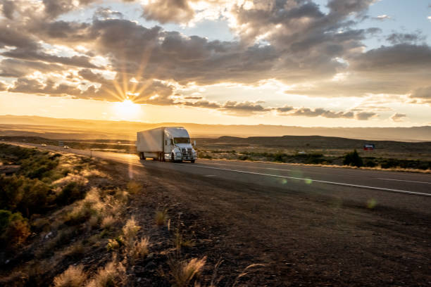 Long Haul Semi Truck Speeding Down a Four Lane Highway To Delivery Heavy Cargo stock photo