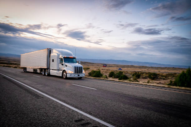 Long Haul Semi Trucks Speeding Down a Four Lane Highway To Delivery Their Loads stock photo