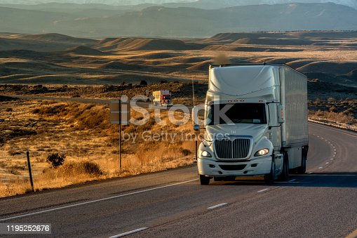 Long Haul Semi-Truck Rolling Down a Four-Lane Highway at Dusk