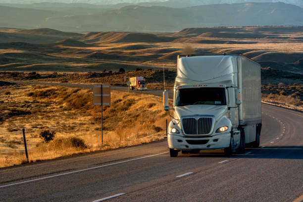 Long Haul Semi-Truck Rolling Down a Four-Lane Highway at Dusk stock photo