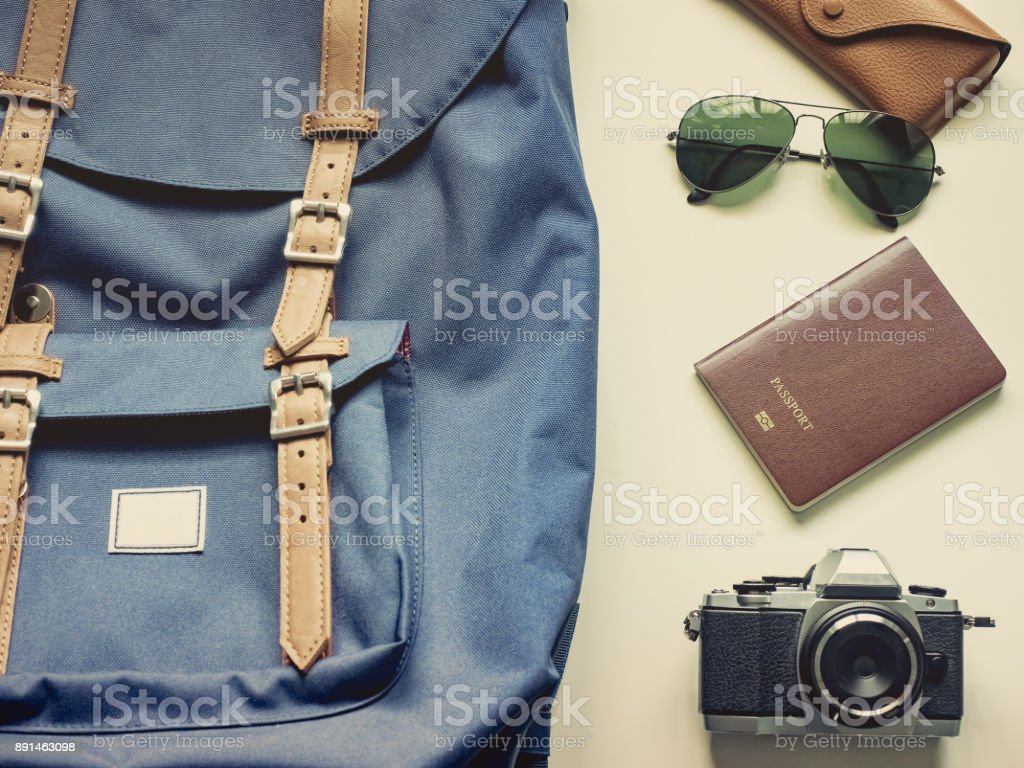 long holiday travel flat lay concept from blue backpack and lather strap for man with retro camera , sunglasses with case and passport put on isolated white background stock photo