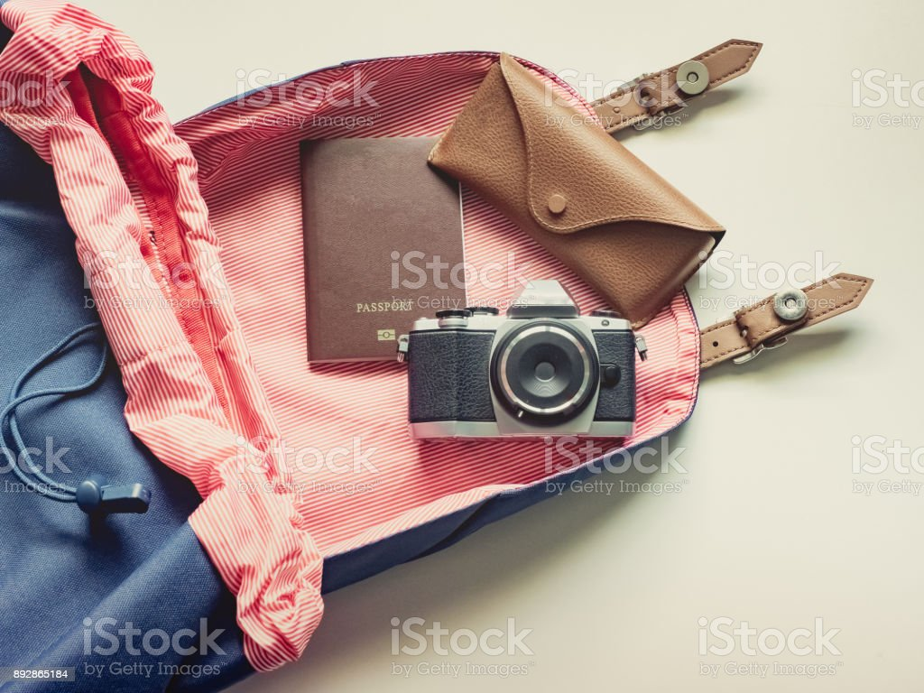 long holiday travel flat lay concept from blue backpack with retro camera , sunglasses with case and passport put on isolated white background stock photo