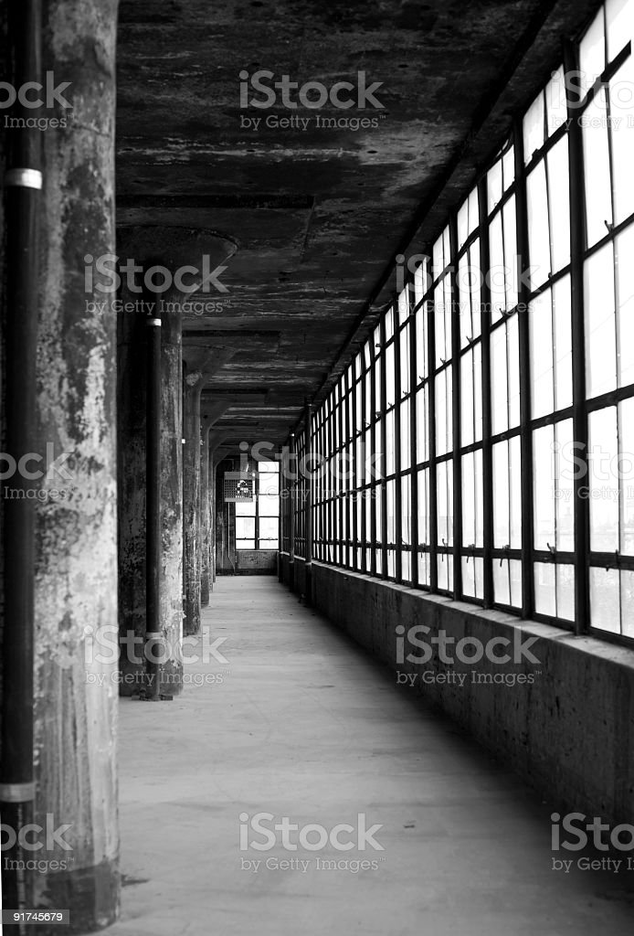Long industrial corridor lined by windows and pillars royalty-free stock photo