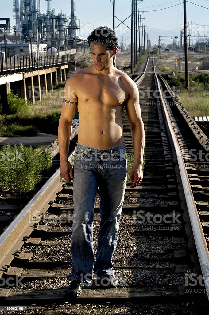 A man walking down the railroad tracks