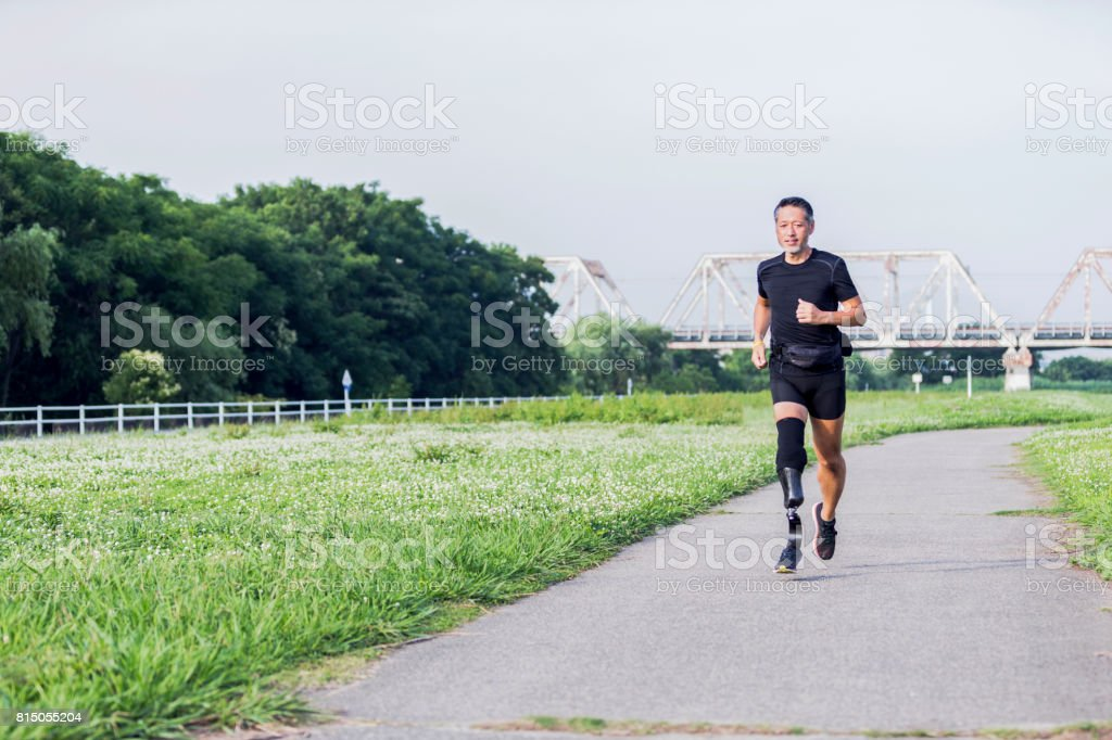 Japanese man with a prothetic leg jogging down a trail.