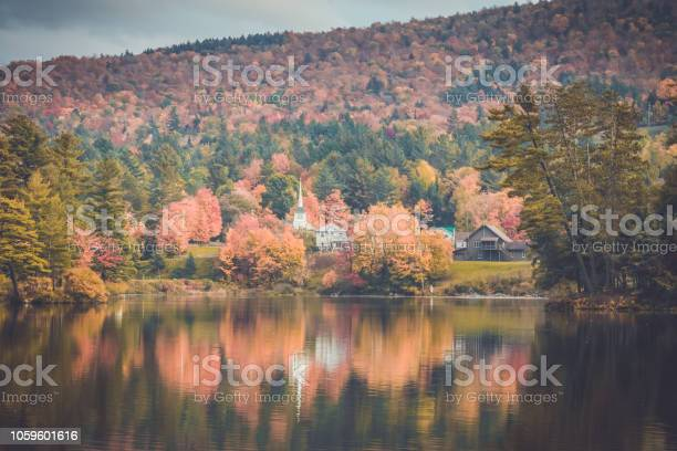 Photo of Long Lake, Adirondacks, NY, in the fall surrounded by brilliant colorful foliage