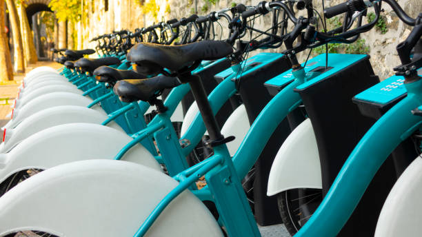 Long line of parked bikes in the automatic bike rental station, in the Park on the background of green trees Environment, Paid, Pollution, Street, Symbol iberian stock pictures, royalty-free photos & images
