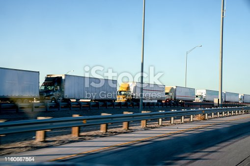 A long line of Semi Trucks waiting at the US side of the International Border crossing into Mexico to transport goods