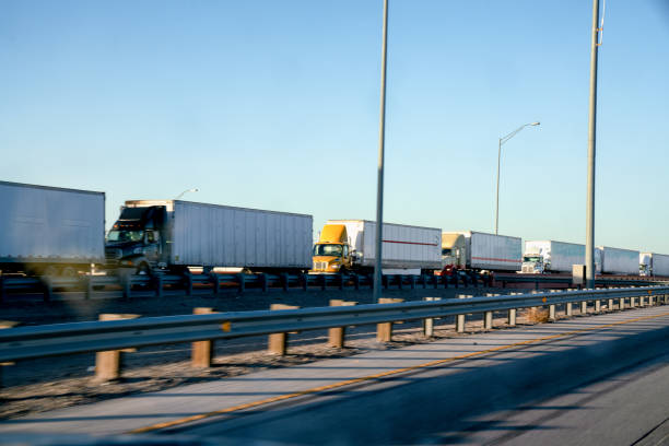 A Long Line Of Semi Trucks Waiting To Cross The Border From The United States Into Mexico A long line of Semi Trucks waiting at the US side of the International Border crossing into Mexico to transport goods frontier field stock pictures, royalty-free photos & images