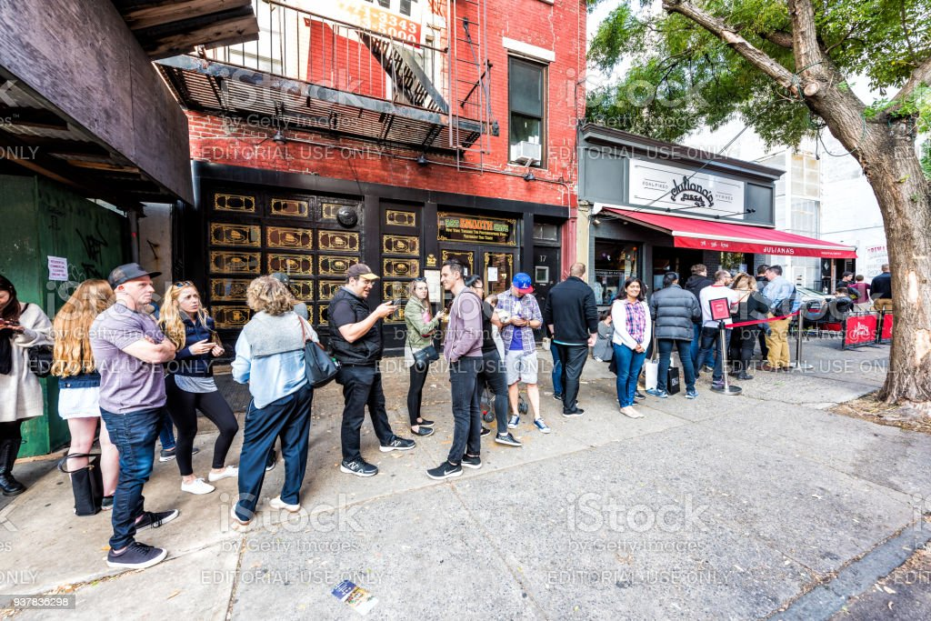 Long line queue of people crowd waiting for famous restaurant food called Juliana's Pizza stock photo