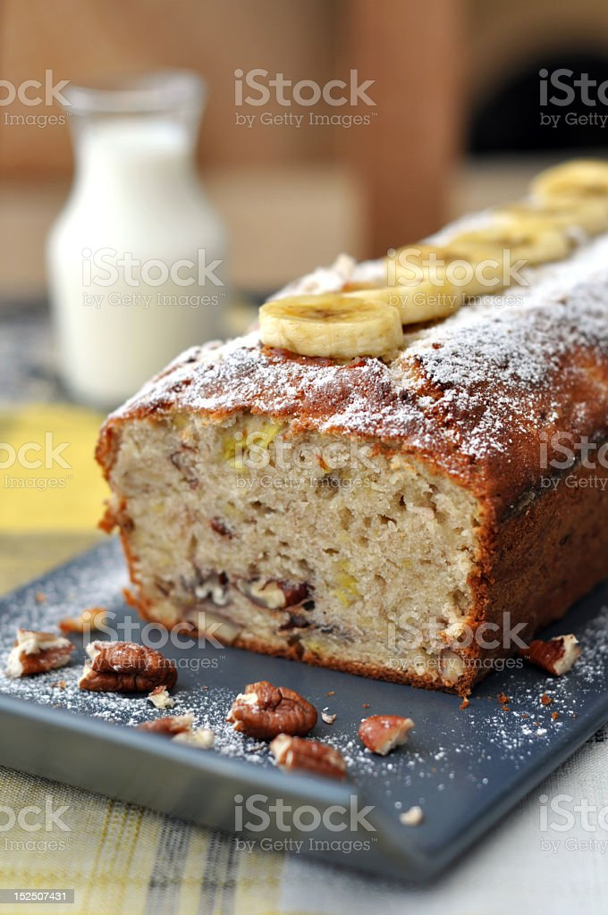 Long loaf of banana bread presented artistically with pecans stock photo