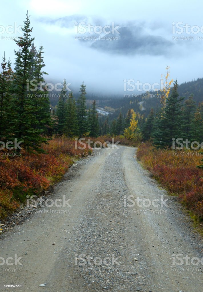 A long lonely road into Alaska's Denali National Park on a foggy day. stock photo