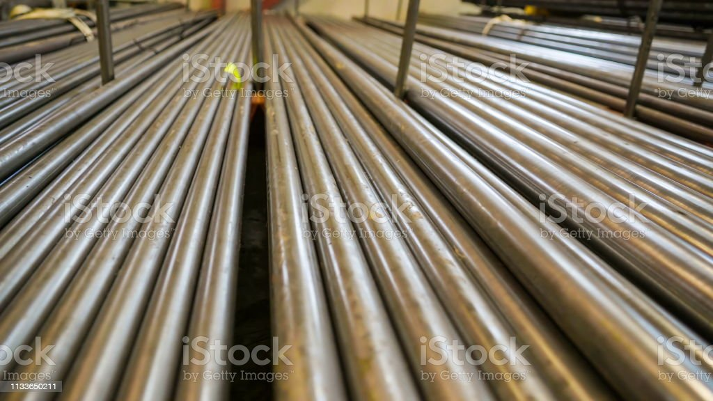 Long metal pipes stored in the room of the steel factory ready for...