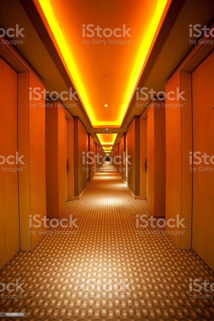 Long, narrow corridor with retro themed carpet and lighting stock photo