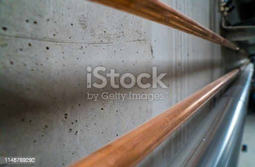 horizontal view of long new shiny copper pipes leading along a concrete cellar wall