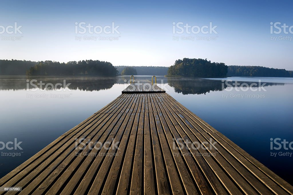 Long pier in a lake with trees royalty-free stock photo