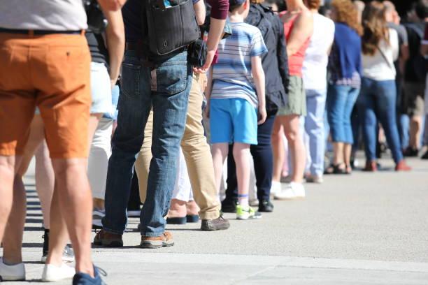 long queue of people waiting in line - queue foto e immagini stock
