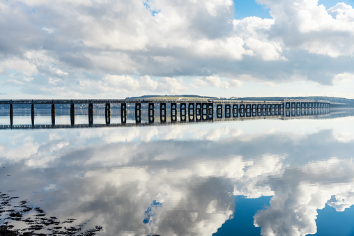 Long Railway Bridge Over A River With Clouds Reflecting In Water Stock Photo - Download Image Now