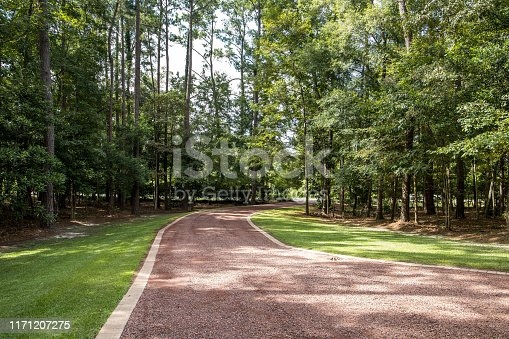 long red gravel driveway to a custom home with trees lining the driveway