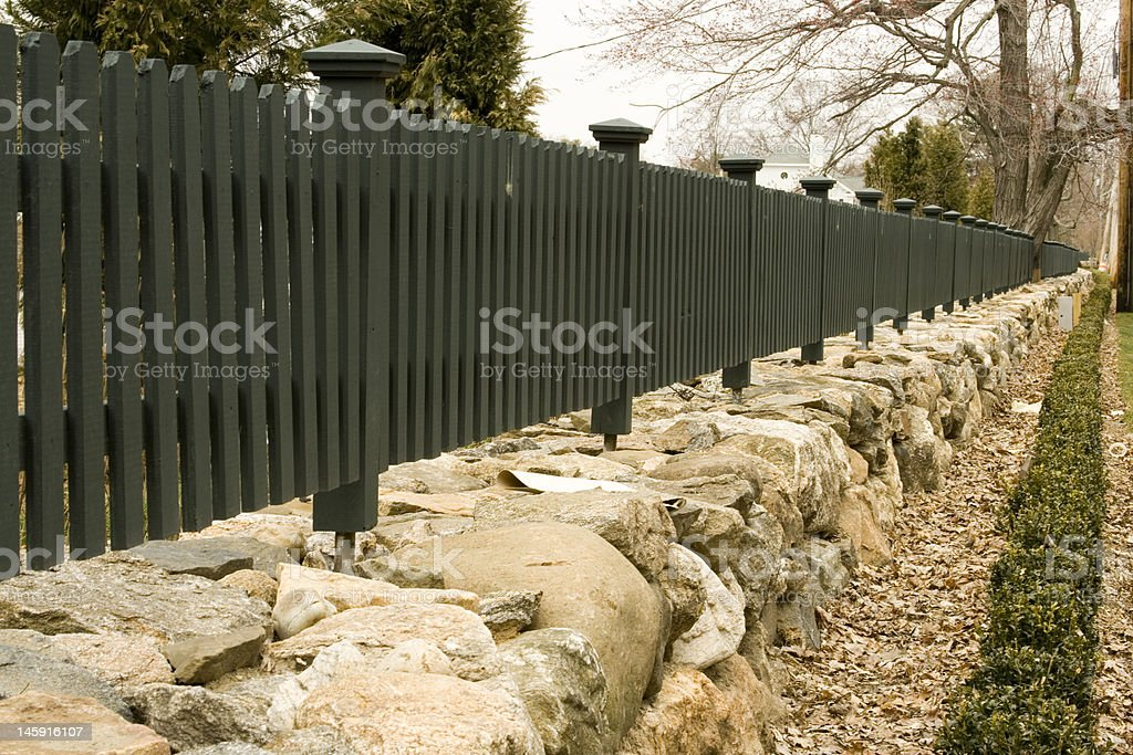 Long retaining wall and wood picket fence royalty-free stock photo