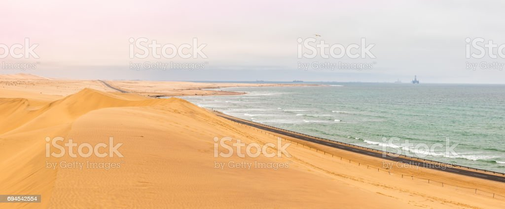 Long road across dunes of Kalahari desert with Atlantic seaside, near to Swakopmund town, Namibia stock photo