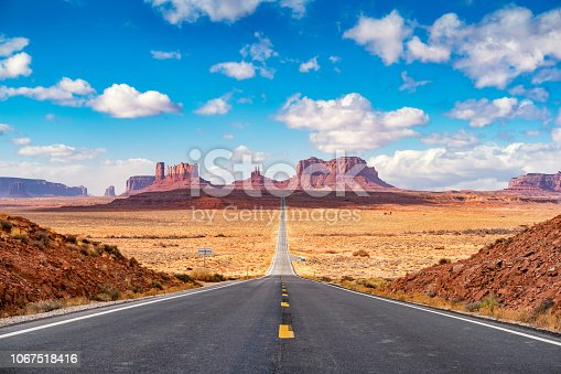 Stock photograph of long road leading towards Monument Valley as seen from Forrest Gump Point, Utah.