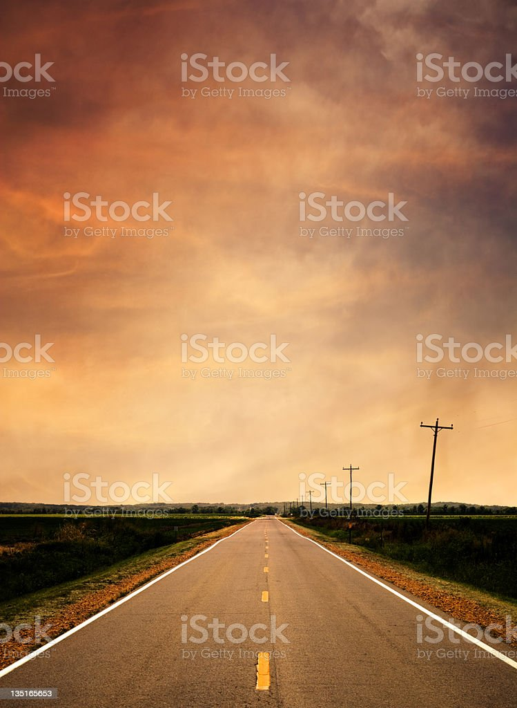 Long road in the country leading off into the sunset royalty-free stock photo