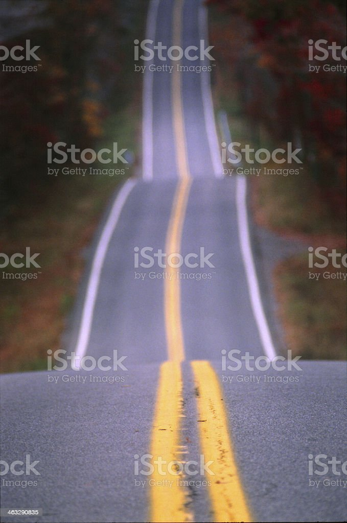 A long road goes in to the distance of many small hills.