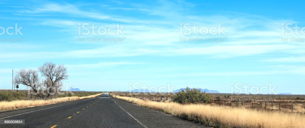 empty road disappearing into infinity in west texas near marfa with...