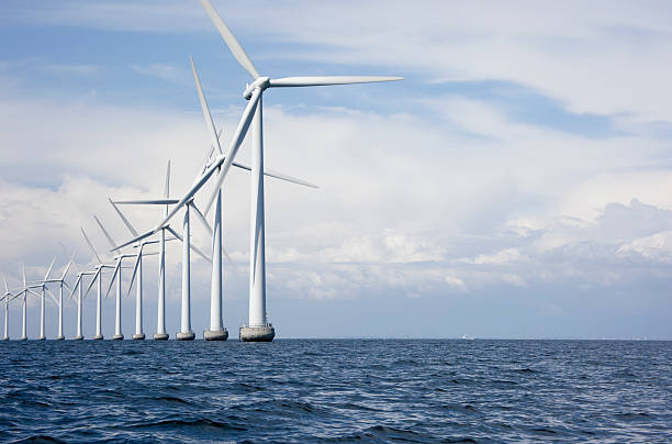 long row a very tall windmills offshore - windmolen stockfoto's en -beelden