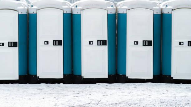 Lange Reihe von mobilen Toiletten außerhalb auf dem schneebedeckten Boden. Bio-Toiletten im freien – Foto