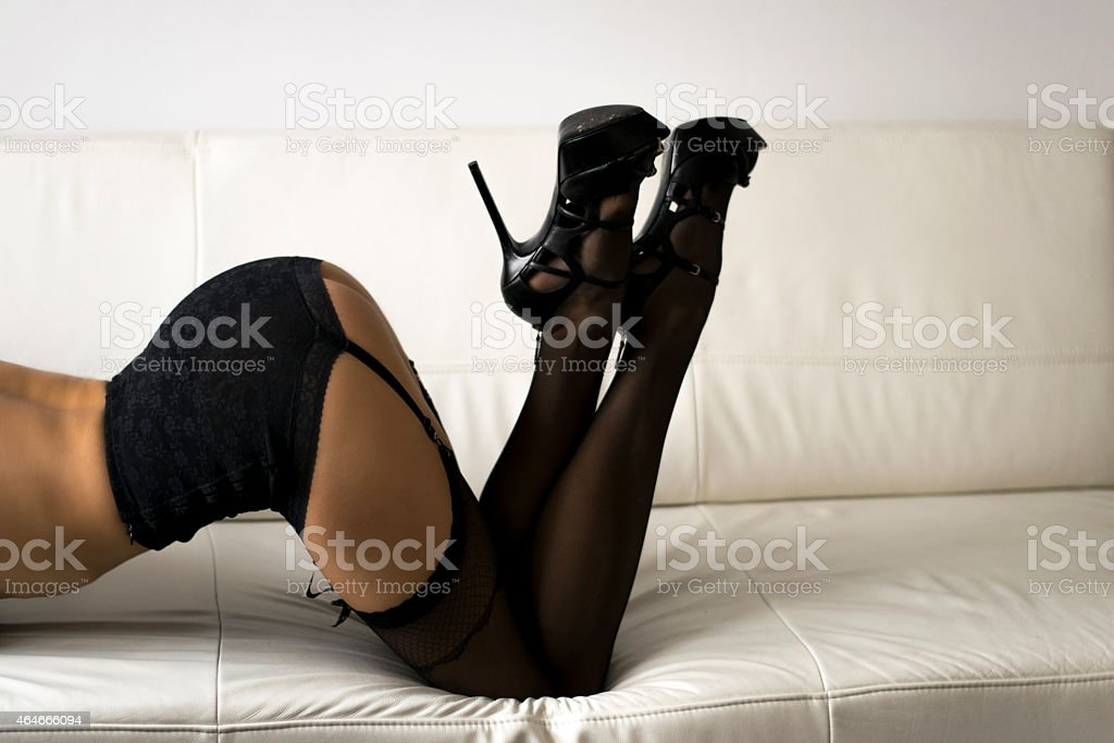 Long sexy Woman legs in black stockings on sofa. stock photo