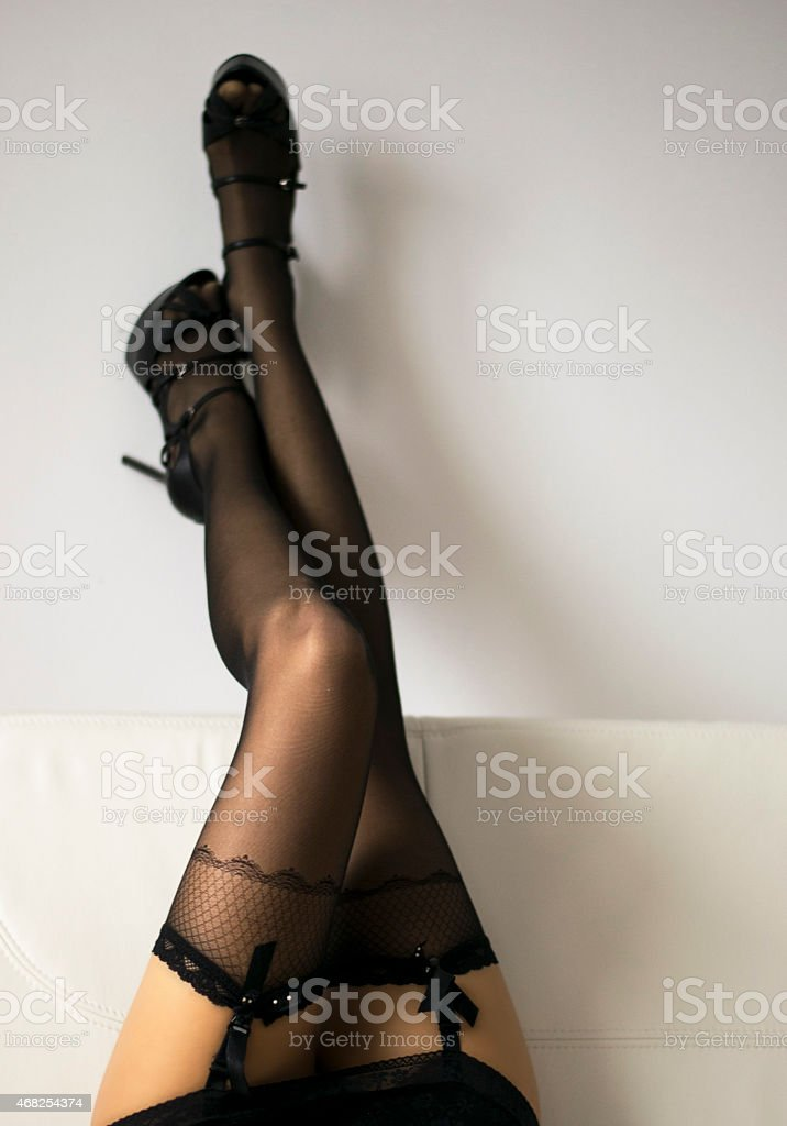 Long sexy Woman legs in black stockings on sofa stock photo