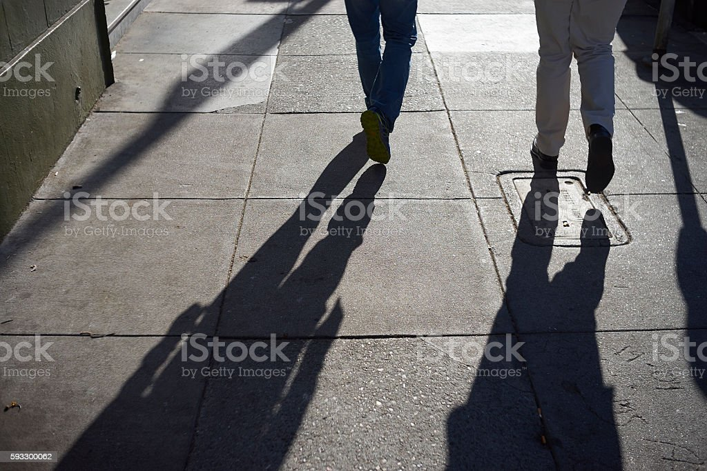 long shadow of people walking on street stock photo