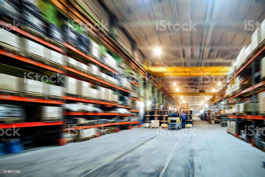 Long shelves with a variety of boxes and containers. Motion blur...
