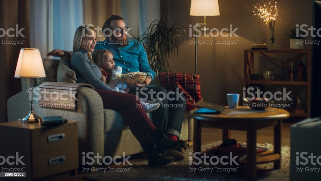 Long Shot of a Father, Mother and Little Girl Watching TV. They Sit on a Sofa in Their Cozy Living Room and Eat Popcorn. It's Evening. stock photo