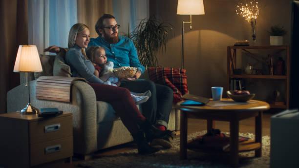 largo tiro de padre, la madre y la niña, viendo la televisión. se sientan en un sofá en su acogedora sala de estar y comen palomitas de maíz. es la noche. - sequence animation fotografías e imágenes de stock