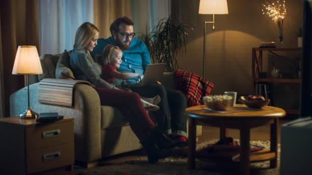 largo tiro de padre, la madre y la niña, viendo la televisión. se sientan en un sofá en su acogedora sala de estar, el padre tiene ordenador portátil sobre las rodillas. es la noche. - sequence animation fotografías e imágenes de stock