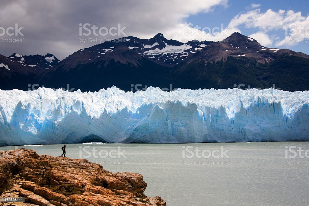 Long shot of man hiking in front of Perito Moreno Glacier stock photo